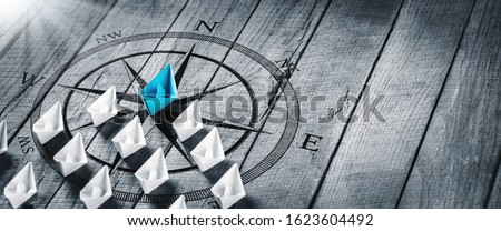 Blue Paper Boat Leading A Fleet Of Small White Boats With Compass Icon On Wooden Table With Sunlight - Leadership Concept #1623604492