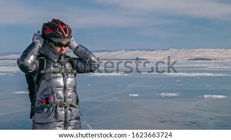 Woman stands near her bike on ice. The girl cyclist stopped to rest. The beautiful view of the sunset. The traveler is ride a cycle. Female is riding bike on the ice. Athlete puts on gear. #1623663724