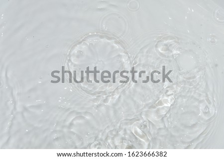 top view Closeup water rings, rippled water on white background. reflections in water. Radial waves from a rain on water. Circles and rings on the puddle.