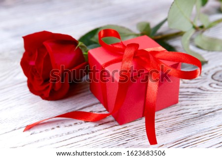 Valentine's day background. On a gray wooden background a red gift box with a ribbon and a red rose. Close-up, horizontal, side view, free space for text.