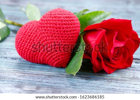 Valentine's day background. On a gray wooden background in the center is a red knitted heart and a red rose. Close-up, horizontal, side view, free space for text.