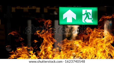 Hot flame fire and green fire escape sign hang on the ceiling in the Warehouse at night. The concept of fire escape training and preparation for evacuation