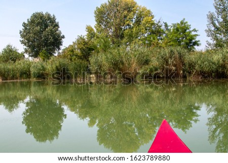Kayak adventure on the Moson Danube river in Hungary. Kayaking on a river with red boat. Beautiful view of nature. Reflection photo. Hungarian tourist and sport destination.