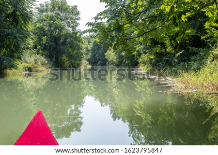 Kayak adventure on the Moson Danube river in Hungary. Kayaking on a river with red boat. Hungarian tourist and sport destination. Beautiful view of nature. Reflection photo.