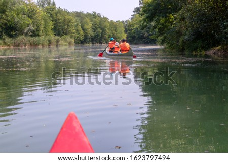 People are kayaking on the river. Family kayak tour on the Moson Danube river in Hungary. Hungarian tourist and sport destination. Beautiful view of wild life of nature.