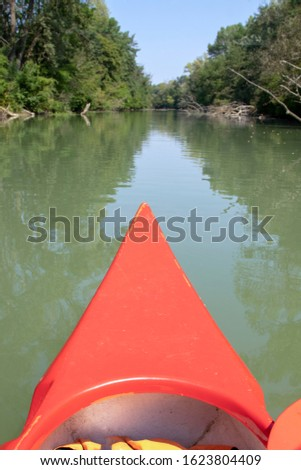 Kayak tour with red boat on the Mosoni-Duna river in Hungary. Beautiful nature photo of hungarian tourist destination. Active recreation background. Adventure in wild life.