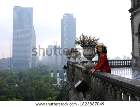 An Asian female tourist posing for a picture on a balcony overlooking the Bosque de Chapultepec or Chapultepec Forest from Chapultepec Castle in Mexico City, Mexico.