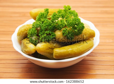 Plate with small canned gherkins on wooden background. #162388652