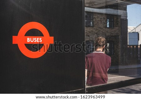 A man talking on a phone while waiting for a bus at a bus stop in London. A bus stop is a designated place where buses stop for passengers to board or alight from a bus #1623963499