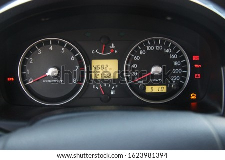 Car dashboard showing the instrument panel with board computer and the basic gauges: water, fuel, speed and tachometer #1623981394