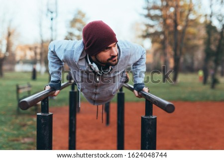 handsome young man jogging outdoors in city park work out in outdoor gym #1624048744