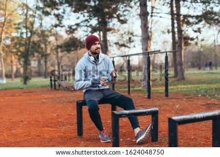 handsome young man jogging outdoors in city park work out in outdoor gym #1624048750