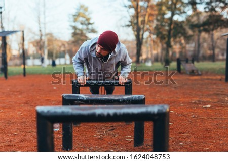 handsome young man jogging outdoors in city park work out in outdoor gym #1624048753