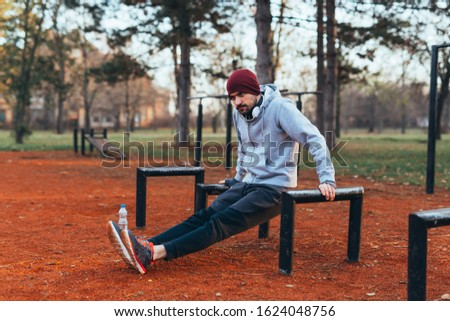 handsome young man jogging outdoors in city park work out in outdoor gym #1624048756