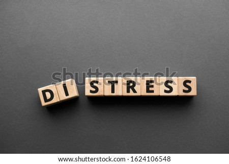 Distress Stress  - words from wooden blocks with letters, distress to stress concept, top view gray background #1624106548