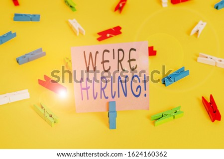 Text sign showing We Re Hiring. Conceptual photo recently employ someone or pay him to do particular job Colored clothespin papers empty reminder yellow floor background office. #1624160362