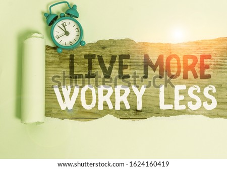 Conceptual hand writing showing Live More Worry Less. Business photo text Have a good attitude motivation be careless enjoy life Alarm clock and torn cardboard on a wooden classic table backdrop. #1624160419