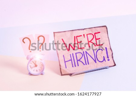 Writing note showing We Re Hiring. Business photo showcasing recently employ someone or pay him to do particular job Alarm clock beside a Paper sheet placed on pastel backdrop. #1624177927
