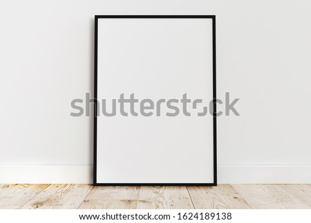 Empty thin black frame on light wooden floor with white wall behind it. Empty poster frame mockup. Empty picture frame mockup. Blank photo frame.