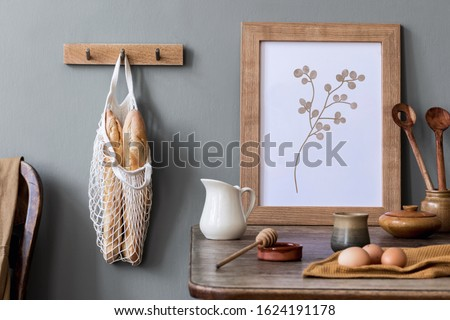 Stylish interior design of kitchen space with mock up photo frame, wooden table, cup of tea, eggs, bagles and kitchen accessories. Cozy home decor of kitchen space. Template.