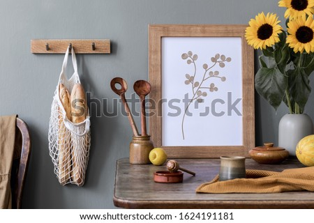 Stylish interior design of kitchen space with wooden table, mock up frame, bag with bagles, honey, sunflowers in vase, vegetables and kitchen accessories. Vintage concept of kitchen space..