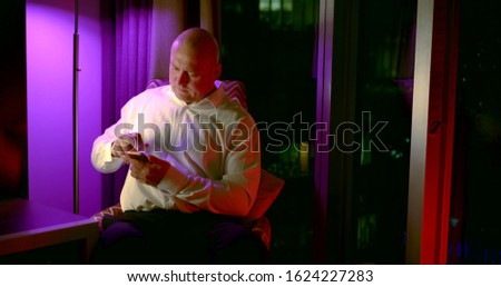 alone man is chatting by messages in smartphone in evening time in his flat, smiling #1624227283