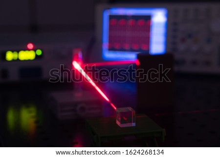 Experiment in optic lab with laser device. Red laser on optical table in physics laboratory #1624268134