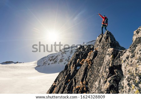 Climber or alpinist at the top of a mountain. A success of mountaineer reaching the summit. Outdoor adventure sports in winter alpine moutain landscape. Sunny day and a climber on a top of a peak. #1624328809