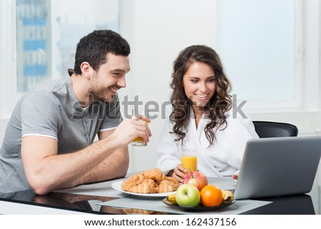 young beautiful couple having breakfast with a laptop #162437156