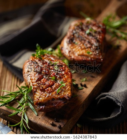Roasted duck breast with the addition of aromatic herbs on a wooden board, close-up