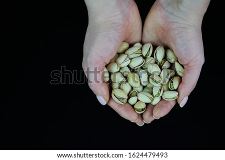 Woman hands holding a wooden bowl with mixed nuts. Healthy food and snack. Walnut, pistachios, almonds, hazelnuts and cashews Royalty-Free Stock Photo #1624479493