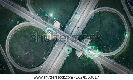 GPS navigation and autonomous driverless transportation concept. Aerial view of transport junction with cars and trucks driving with digital green circles, future global technology on roads. Royalty-Free Stock Photo #1624553017