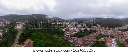 Aerial 360 DEGREES PANORAMA of the historic colonial mining city of Ouro Preto in Minas Gerais, Brazil, with Saint Francis of Paola church and pathway into town in the foreground on an overcast day #1624653253