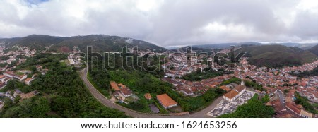 Aerial 360 DEGREES PANORAMA of the historic colonial mining city of Ouro Preto in Minas Gerais, Brazil, with Saint Francis of Paola church in the foreground on an overcast morning #1624653256