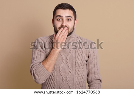 Emotive positive young male covering mouth, trying to stop laughter or hide smile, hearing something hilarious while stands over beige background, guy wearing knitted sweater. People emotions concept. #1624770568