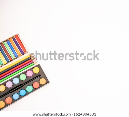 Flat lay of water colours, colouring pencils and coloured chalk on a pure white background with copy space #1624804531
