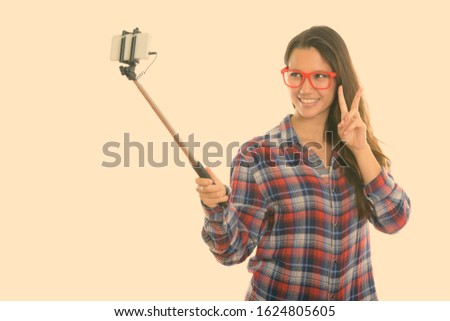 Young happy woman smiling while taking selfie picture with selfie stick and giving peace sign