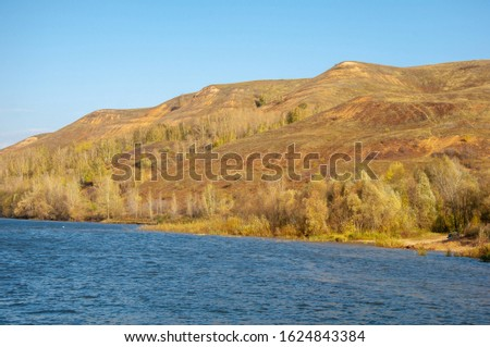 Autumn landscape, dark blue water, last warm days, river, trees, windy weather, yellow-red autumn leaves #1624843384