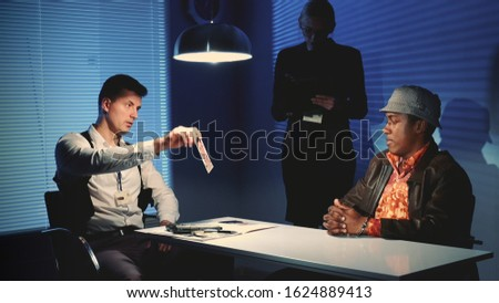 Medium shot of Detective showing picture of suspected robber's accomplice during interview in police office. In the background there is a female detective writing notes of the interrogation.