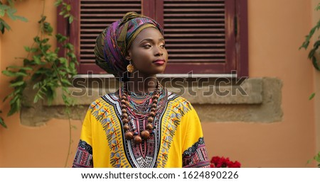 Portrait shot of attractive and stylish young African woman in traditional outfit looking at the side.  Royalty-Free Stock Photo #1624890226