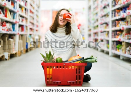 A girl in a jeans and white sweater is citing at the supermarket with a basket of a fruits and veggies, holding a big pepper and smiling. A concept of a groceries, healthy eating, dieting and diets.   #1624919068