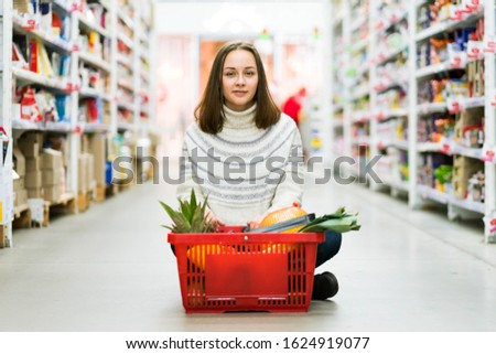 A girl in a jeans and white sweater is citing at the supermarket with a basket of a fruits and veggies and smiling. A concept of a groceries, healthy eating, dieting and diets.  #1624919077