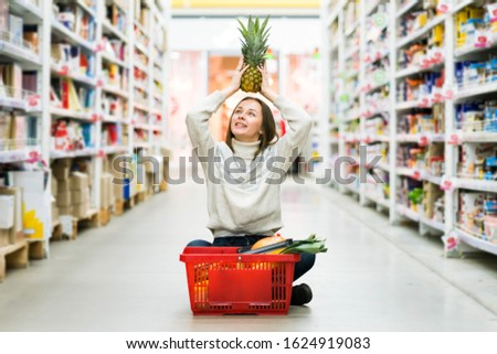 A girl in a jeans and white sweater is citing at the supermarket with a basket of a fruits and veggies and smiling. A concept of a groceries, healthy eating, dieting and diets.  #1624919083