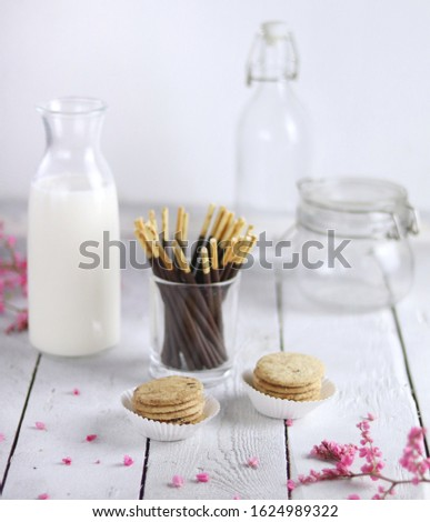 Stick biscuit and round biscuit with a bottle of fresh milk on the white wooden table #1624989322