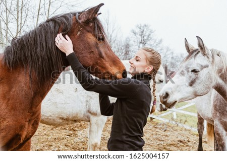 Young girl poses with beautiful, gougers, well grown horse. Action happens in unique farm, special for horses and riding.