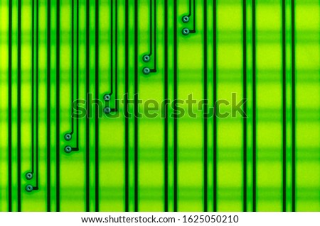 Circuit board as an abstract background, shot with backlight on the lumen. Yellow-green shades, electrically conductive circuits are arranged vertically. #1625050210