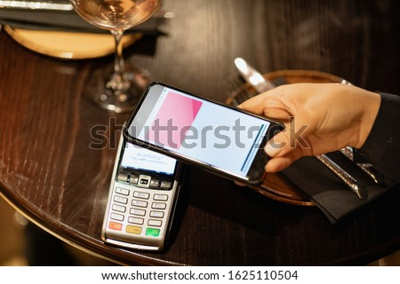 An unrecognizable person using a mobile phone to pay for a meal. #1625110504