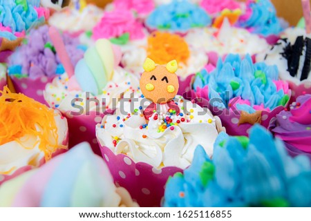 The cup cake bears a beautiful color in the middle of the picture and there are blurry images of the various cup cakes around.