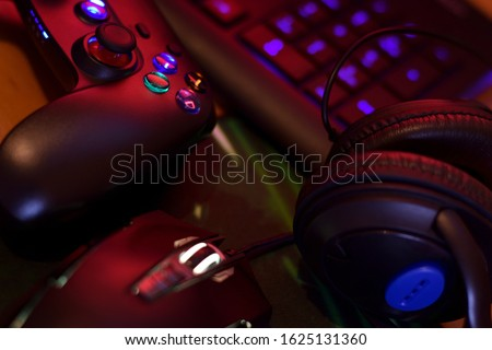 Modern gamepad and gaming mouse lies with keyboard and headphones on table in dark playroom scene. Background composition for video gaming and esports design