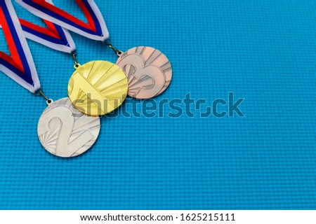 Gold silver and bronze medal on blue background. Medal schedule concept photo, empty edit space
